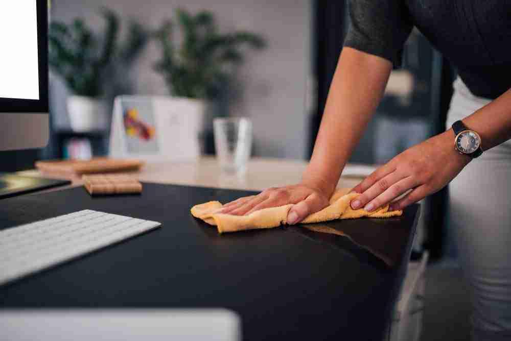 woman wiping down desk